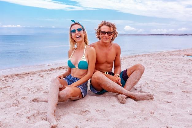 Portret van een jong koppel in liefde op het strand en genieten van tijd samenzijn. jong koppel plezier op een zandige kust.