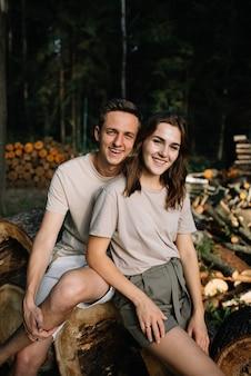 Portret van een jong koppel verliefd op gekapte bomen in het bos.