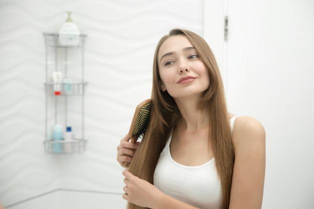Portret van een jong lachend meisje haar haar poetsen