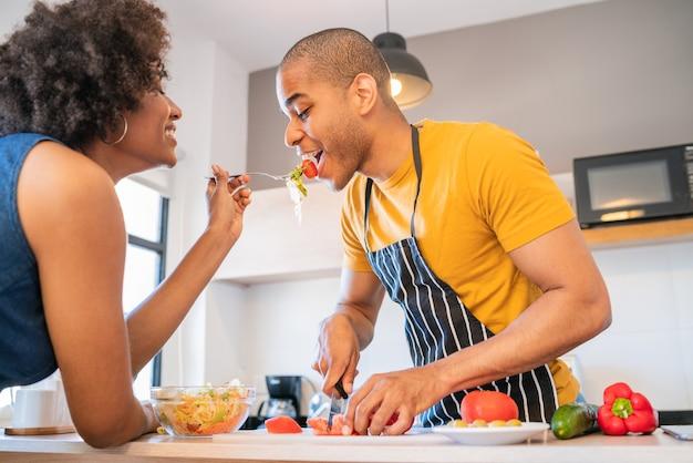 Portret van een jong latijns paar dat samen in de keuken thuis kookt