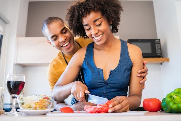 Portret van een jong latijns paar die samen in de keuken thuis koken. relatie-, kook- en levensstijlconcept.