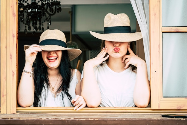 Portret van een jong leuk stel meisjes die grappige uitdrukkingen doen die ogen verbergen met hoeden
