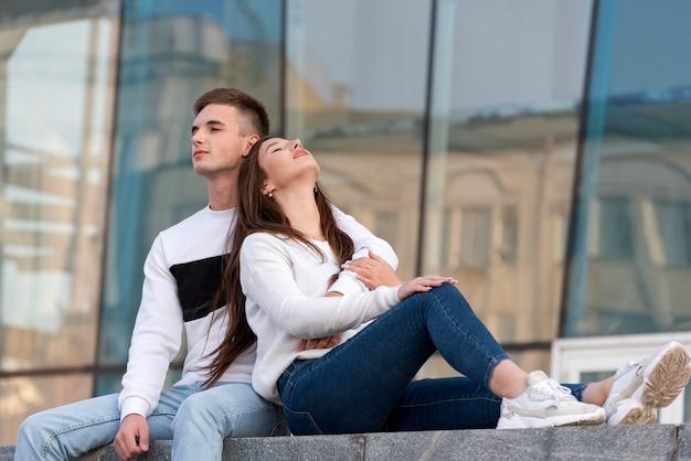 Portret van een jong liefdevol stel met rust binnen in de stad. meisje leunde op de schouder van de jongen. studenten liefde.