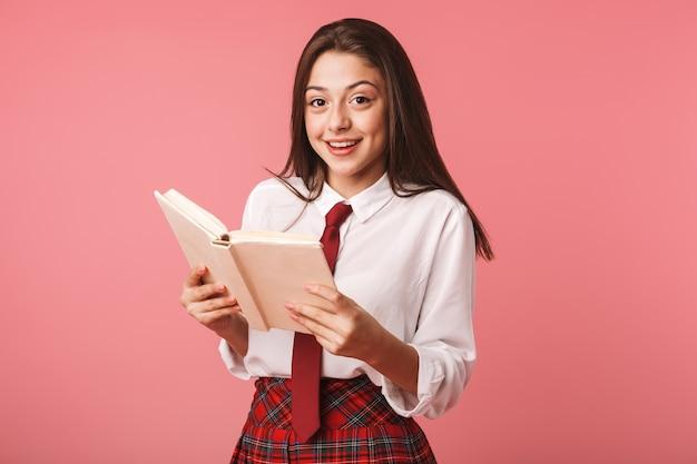 Portret van een jong meisje 15-16 jaar in schooluniform leesboek, terwijl status geïsoleerd over rode muur