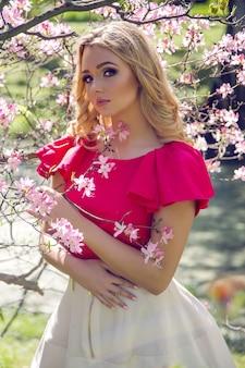 Portret van een jong meisje blondjes met make-up in de kers sakura roze wit in een witte rok en roze top