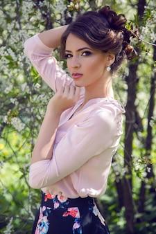 Portret van een jong meisje bruin haar met make-up in de kers sakura roze, wit in een blauwe rok en roze blouse