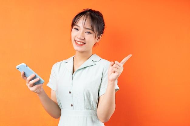Portret van een jong meisje dat de telefoon gebruikt en naar rechts wijst, geïsoleerd op een oranje achtergrond