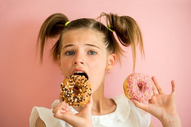Portret van een jong meisje dat door twee roze donuts kijkt