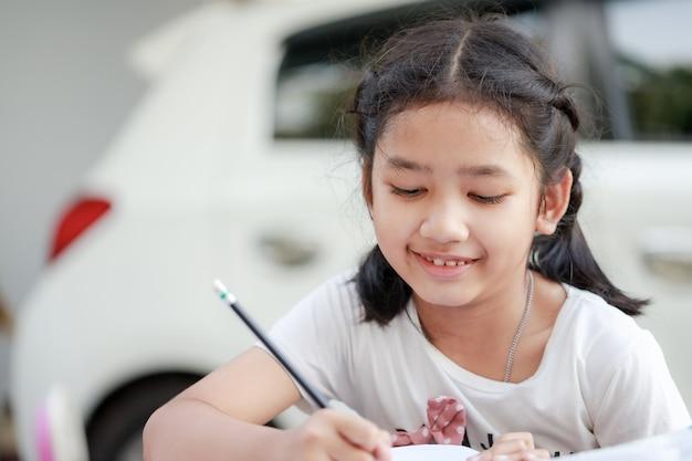 Portret van een jong meisje dat haar huiswerk doet