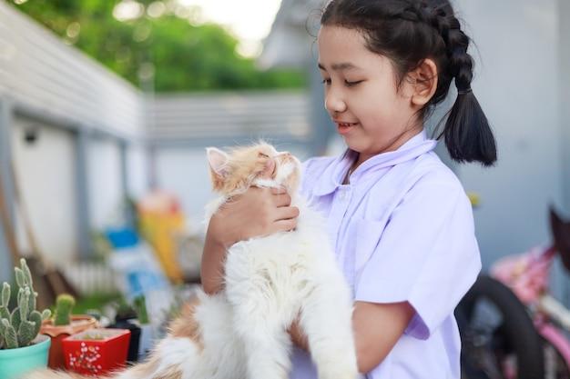 Portret van een jong meisje dat haar kat houdt