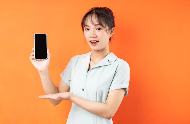 Portret van een jong meisje dat het telefoonscherm toont, geïsoleerd op een oranje achtergrond