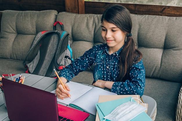 Portret van een jong meisje dat huiswerk doet