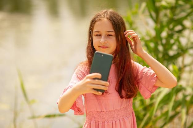 Portret van een jong meisje dat in de zomer selfie-foto maakt in de buurt van de rivier.