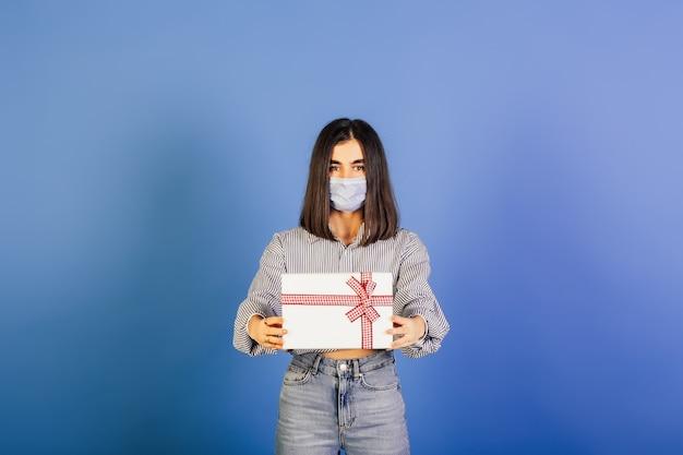 Portret van een jong meisje dat in medisch masker witte giftdoos houdt.