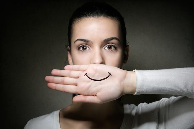 Portret van een jong meisje dat met haar hand huilt en haar mond bedekt