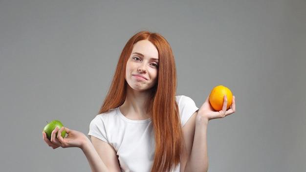 Portret van een jong meisje dat op een grijze achtergrond staat, vroeg zich af welk fruit gezonder apple of sinaasappel is