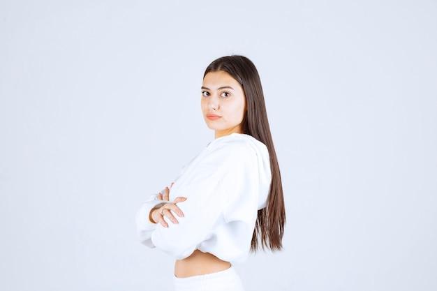 Portret van een jong meisje dat staat en naar de camera kijkt.