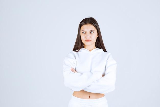Portret van een jong meisje dat staat en wegkijkt.