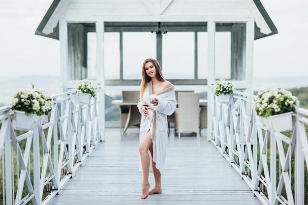 Portret van een jong meisje heeft een ochtend in de buurt van de zee, sta op en blijf op het luxe terras.