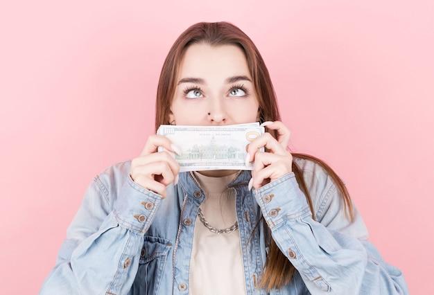 Portret van een jong meisje in denimoverhemd dat een pak dollars ruikt. winkelen, budget en zakgeld concept.