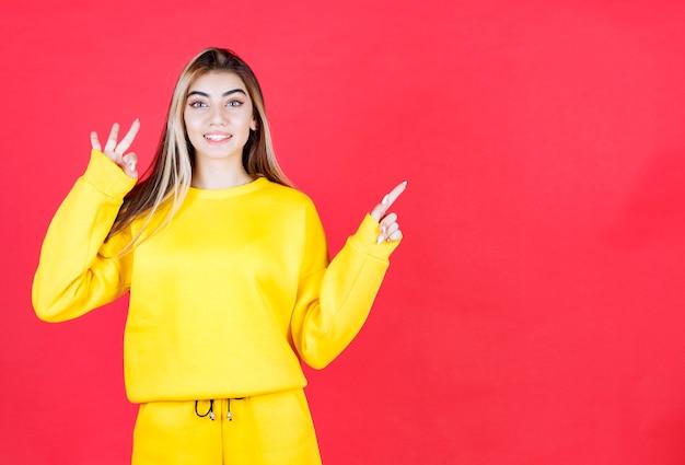 Portret van een jong meisje in een gele outfit die op een rode muur staat