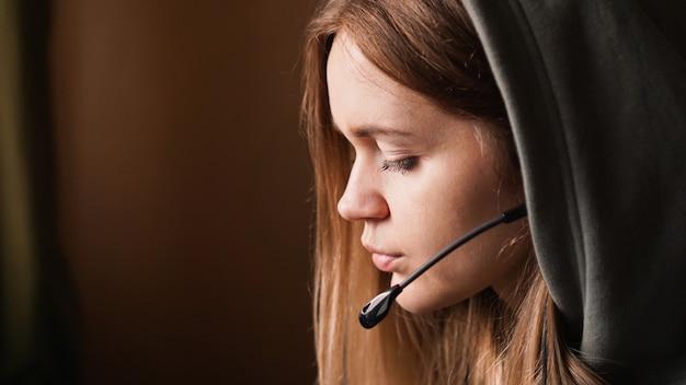 Portret van een jong meisje in een hoodie en met een headset. callcenter medewerker. mooi meisje in de kap. thuiswerken op afstand. bruine tinten foto's
