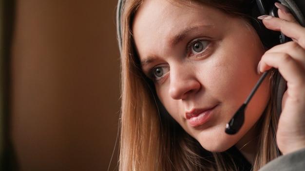 Portret van een jong meisje in een hoodie en met een headset. callcenter medewerker. thuiswerken op afstand. bruine tinten foto's
