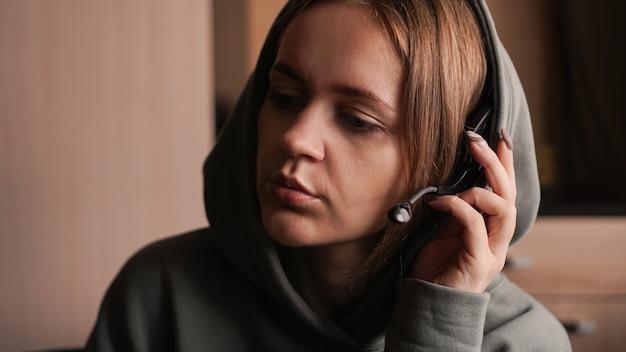 Portret van een jong meisje in een hoodie en met een headset. callcenter medewerker. ze houdt het oortje vast om de cliënt beter te kunnen horen. communicatieproblemen. thuiswerken op afstand. bruine tinten foto's