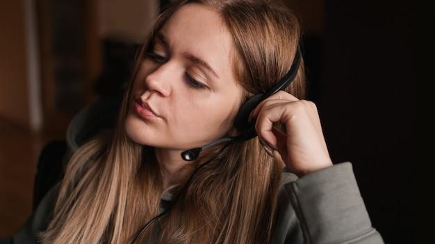Portret van een jong meisje in een hoodie en met een headset. ze luistert met een vermoeide blik naar de cliënt. eentonig werk. callcenter medewerker. thuiswerken op afstand. bruine tinten foto's