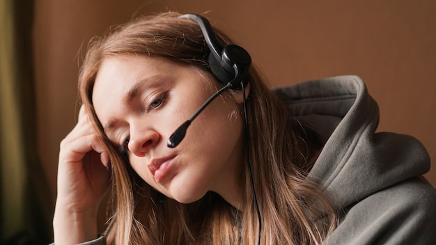 Portret van een jong meisje in een hoodie en met een hoofdtelefoon vermoeide call centrearbeider