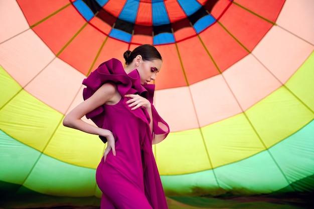 Portret van een jong meisje in een karmozijnrode jurk met een aerostat