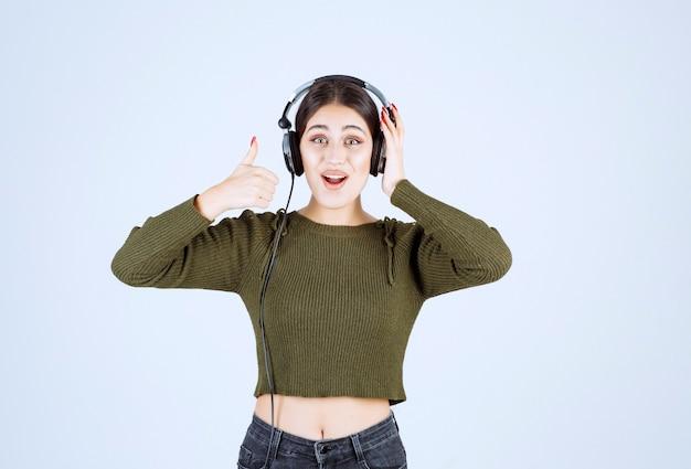 Portret van een jong meisje in een koptelefoon die naar muziek luistert en duimen opgeeft.