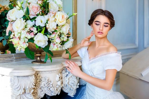 Portret van een jong meisje in een mooie jurk in het interieur, vrouwelijke schoonheid