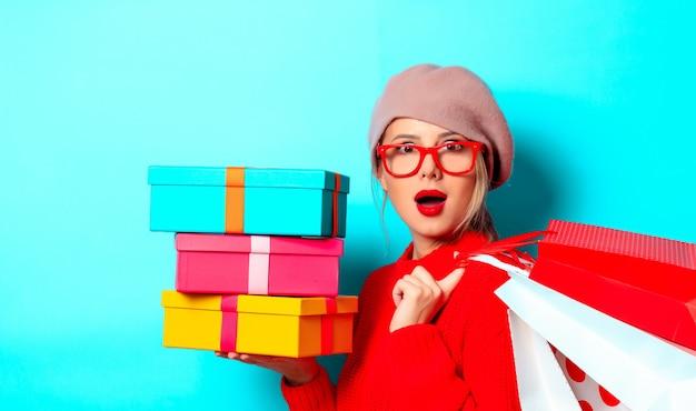 Portret van een jong meisje in een rode trui met geschenkdoos en boodschappentassen op blauwe achtergrond