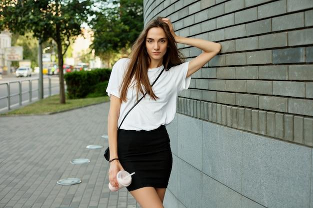 Portret van een jong meisje in een wit t-shirt met een milkshake