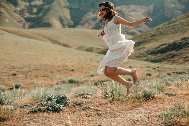 Portret van een jong meisje in een witte doorzichtige kleding in boho of hippiestijl