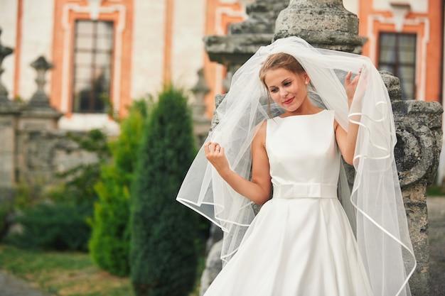 Portret van een jong meisje in een witte trouwjurk en een lange sluier