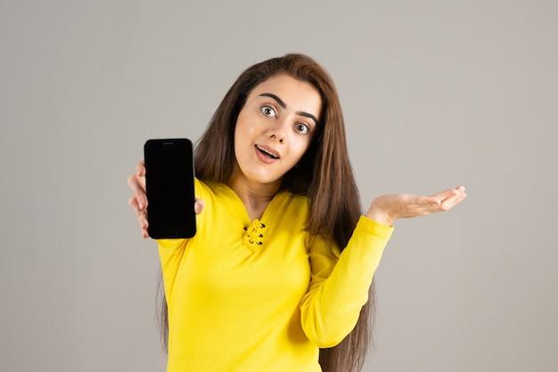 Portret van een jong meisje in gele top poseren met mobiele telefoon op grijze muur.