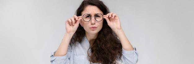 Portret van een jong meisje in glazen. mooi jong meisje op een grijze achtergrond. een jong meisje in een lichte blouse en een donkere broek.
