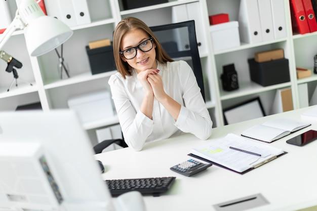 Portret van een jong meisje in het kantoor aan de tafel.