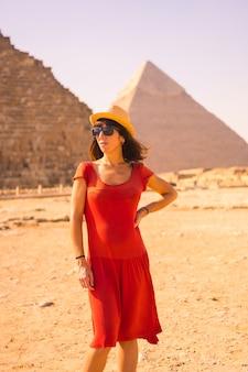 Portret van een jong meisje in rode jurk bij de piramide van cheops de grootste piramide. de piramides van gizeh zijn het oudste grafmonument ter wereld. in de stad caïro, egypte