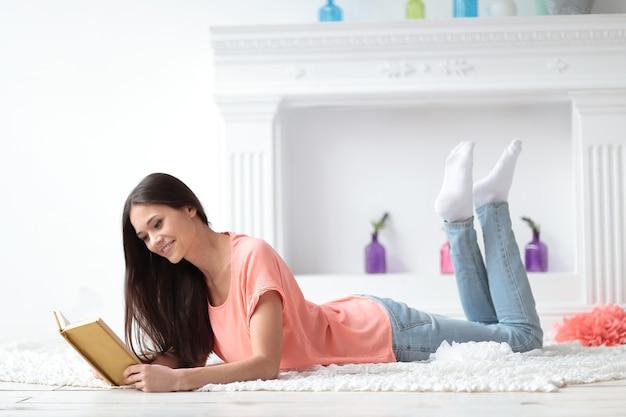 Portret van een jong meisje leesboek liggend op de vloer in de woonkamer.