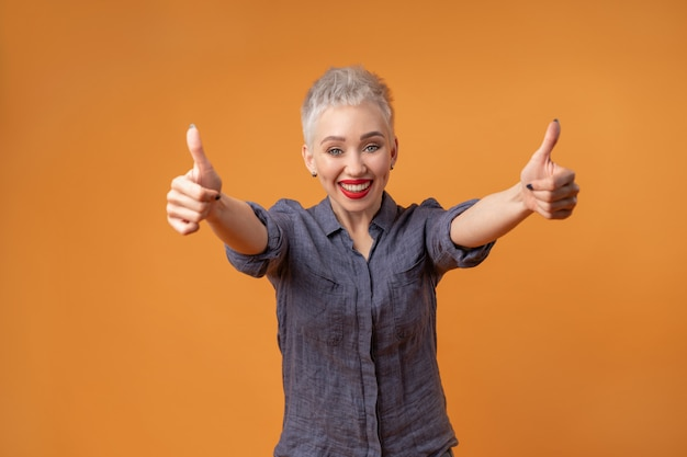 Portret van een jong meisje met blond kort kapsel camera kijken en lachen