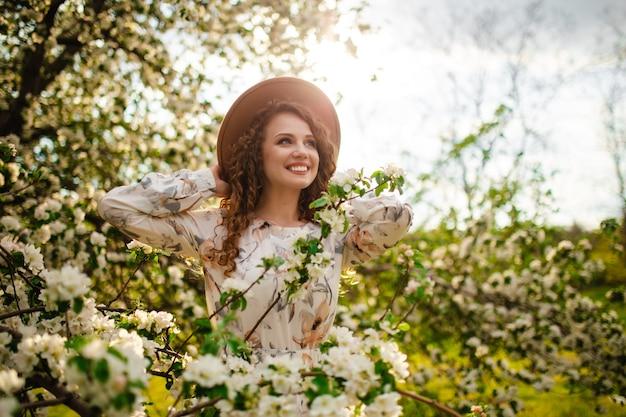 Portret van een jong meisje met donker haar dat lacht en plezier maakt in het midden van een bloeiende boom omringd door veel witte bloemen. vrouw in beige hoed en witte jurk in het lentepark.