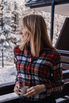 Portret van een jong meisje met een kopje thee van de winterbergen, zakopane, koscielisko. wintervakantie en wintervakantie concept