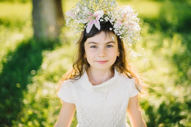 Portret van een jong meisje met een krans van bloemen op haar hoofd op een weide