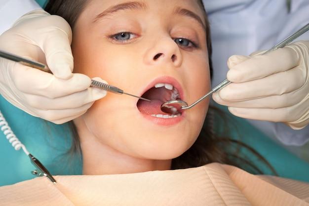 Portret van een jong meisje met een tandartsonderzoek