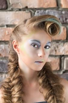 Portret van een jong meisje met gekleurde make-up en blonde vlechten.