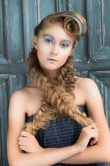 Portret van een jong meisje met gekleurde make-up en blonde vlechten