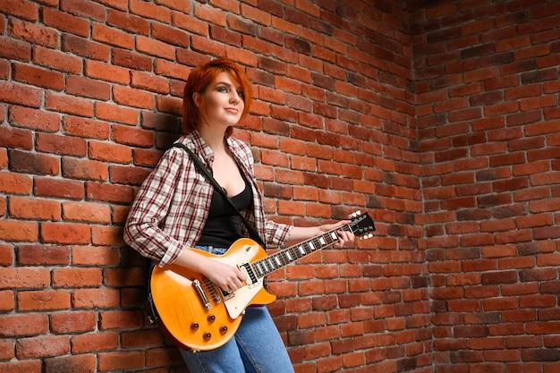 Portret van een jong meisje met gitaar op bakstenen achtergrond.
